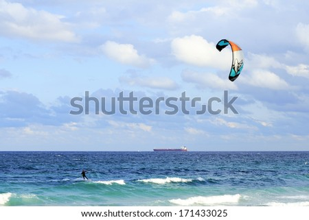 FORT LAUDERDALE, FLORIDA - FEBRUARY 9, 2013: A kiteboarder sailing off the blue green Atlantic ocean coast in the morning with a red orange tanker cargo ship traveling far off in the background. - stock photo