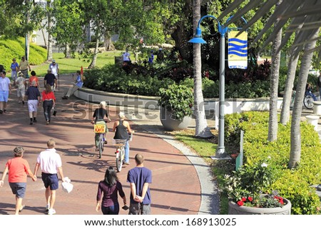 FORT LAUDERDALE, FLORIDA - FEBRUARY 3, 2013: Lots of people enjoying walking and biking on the brick walkway that travels along beautiful Riverwalk park in downtown on a sunny and warm winter day.  - stock photo