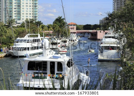 FORT LAUDERDALE, FLORIDA - FEBRUARY 3: Many boats, people and a paddle boarder enjoying winter recreation in the Riverwalk public park area of downtown February 3, 2013 in Ft Lauderdale, Florida.  - stock photo