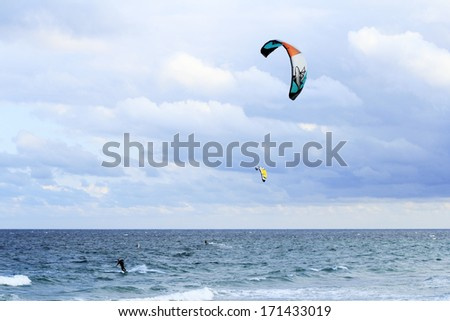 FORT LAUDERDALE, FLORIDA - FEBRUARY 9, 2013: Two kite surfers having fun kiteboarding with colorful kites on the Atlantic ocean on a windy and partly cloudy day winter morning.