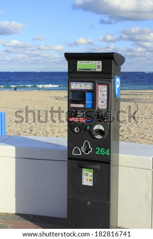 FORT LAUDERDALE, FLORIDA - JANUARY 23, 2014: Electronic parking machine that has a variety payment options, located in front of a white wall in front of the Atlantic Ocean and beach on a sunny day.  - stock photo