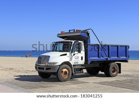 FORT LAUDERDALE, FLORIDA - JANUARY 28, 2014: Parked on a wooden platform just north of Fort Lauderdale Beach Park a white and blue dump truck sits ready for work with a view of the Atlantic ocean.  - stock photo