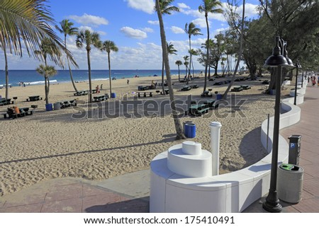 FORT LAUDERDALE, FLORIDA - JANUARY 23, 2014: People relaxing in and near a large area with few dozen green picnic tables near small barbecue grills at Fort Lauderdale beach park on a sunny winter day  - stock photo