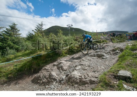 FORT WILLIAM 2014 UCI WORLD CUP, SCOTLAND - 8 JUNE 2014: Downhill World Cup. Competitor in the Junior Mens event races down the track, to finish in 9th place - stock photo