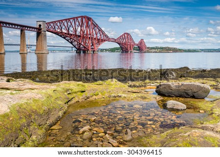 Forth Bridge at low tide / The famous Forth Cantilever Railway Bridge spans the Firth of Forth on a sunny day with a rock pool in the foreground - stock photo