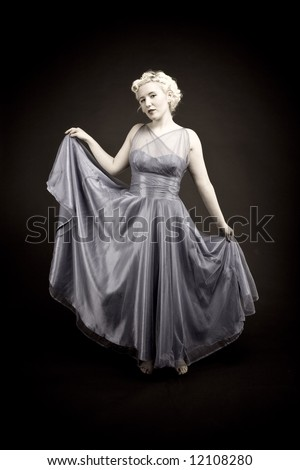 Forties hollywood a beautiful woman shows off her gown. strong eye contact. Minimal lighting and washed out colour. - stock photo