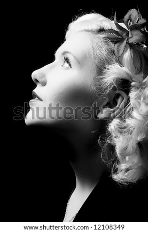 Forties hollywood a beautiful woman stares out of frame. Minimal lighting and strong contrast. black and white - stock photo