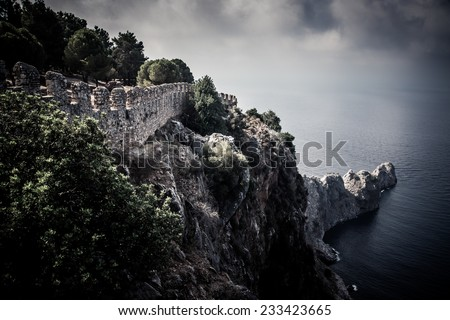 fortification on the edge of a cliff into the sea leaving. dramatic Sky - stock photo