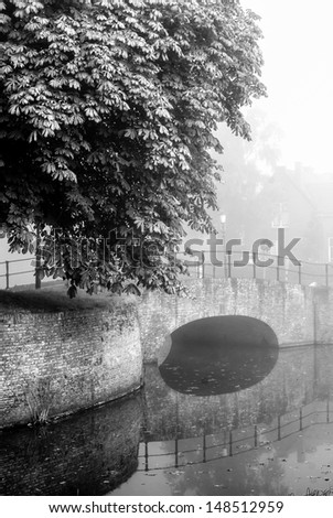 fortified bridge reflection in water - stock photo