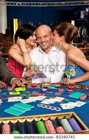 fortunate gambler surrounded by seductive elegant women - stock photo