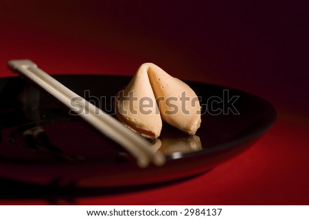 Fortune cookie on black plate with red background - stock photo