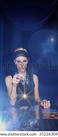 Fortune teller forecasting the future with pendulum against large hanging curtain - stock photo