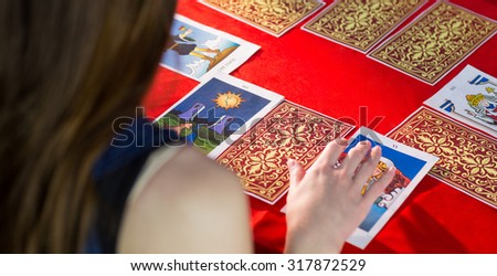 Fortune teller using tarot cards on red table - stock photo