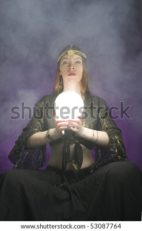 Fortune-teller with lit crystal ball. - stock photo
