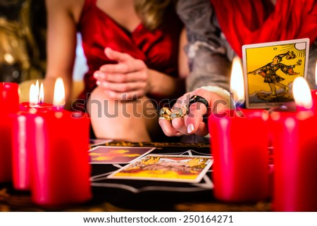 Fortuneteller laying Tarot cards with client on pentagram, candles are burning - stock photo