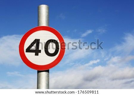 Forty miles per hour speed limit sign against a partly cloudy sky.  - stock photo