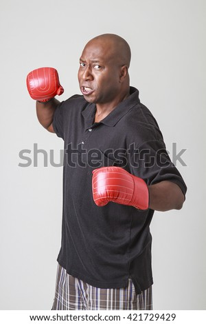 forty something bald black man wearing a black polo and red boxing gloves, throwing a punch