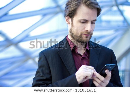 Forty years old businessman standing inside modern office building looking on a mobile phone - stock photo