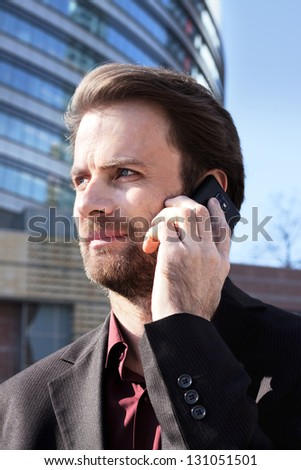 Forty years old businessman standing outside modern office building talking on a mobile phone - stock photo