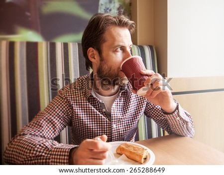 Forty years old caucasian man in casual outfit drinking coffee and eating sandwich in a cafe. City lifestyle - breakfast or lunch. - stock photo