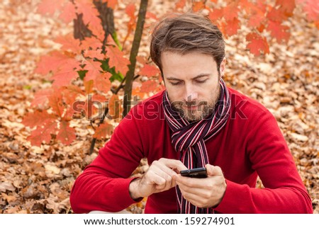 Forty years old caucasian man looking on a mobile phone while sitting outdoor in an autumn park - stock photo