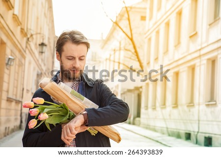 Forty years old caucasian man with baguette, newspaper and flower bouquet looking at watch. Street and city buildings as background.  - stock photo