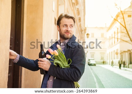 Forty years old caucasian man with wine and flower bouquet ringing doorbell. Date or celebration visit concept. Street and city buildings as background.  - stock photo