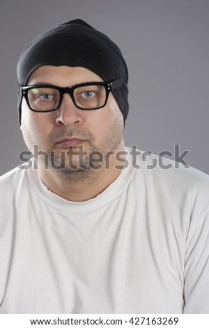 Forty years old man wearing white t-shirt black frame glasses and black skull hat looking depressed and for someone else help