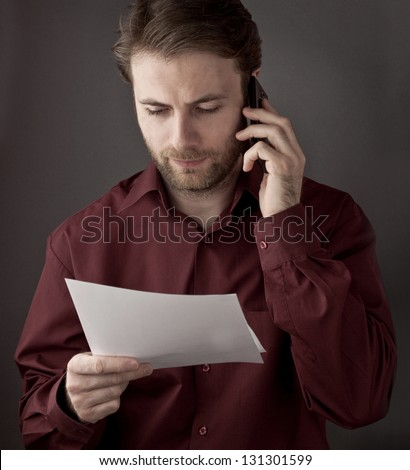 Forty years old office worker reading paper documents during mobile phone conversation - checking terms of agreement - stock photo