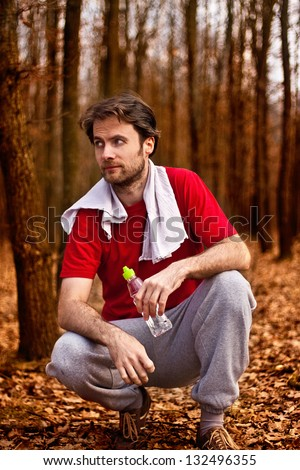 Forty years old runner man drinking water and having a rest after jogging workout in autumn forest - stock photo