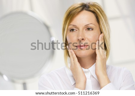 Forty years old woman and mirror