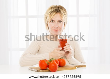Forty years woman  and tomatoes and tomato juice - stock photo