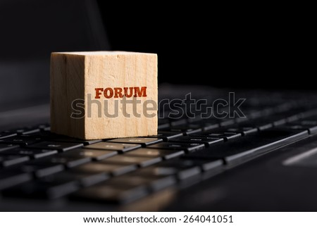 Forum, communication and online support concept with a wooden cube resting on a black computer keyboard with the word - Forum - in red over a dark background with copyspace. - stock photo