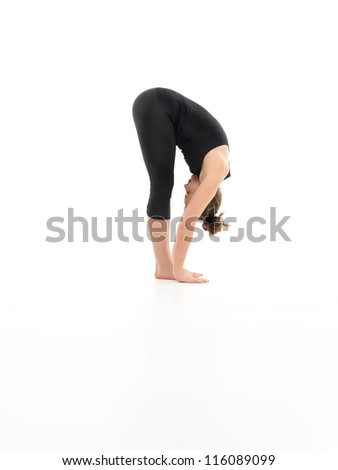 forward bending yoga pose, shown by younf female, dreesed in balck, on white background, side view - stock photo