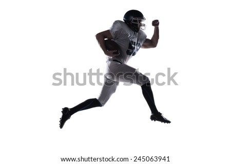 Forward to the victory!  Side view of American football player holding ball and jumping against white background  - stock photo