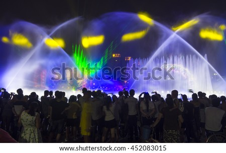 FOSHAN, CHINA - July 9, 2016: To enrich citizens' life, the government in the mandarin park installed sprinkler performance, once every night, has attracted thousands of people watched. - stock photo