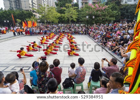 FOSHAN, CHINA - November 19, 2016:In order to enrich people's cultural life, 27 young kungfu team perform kungfu in the park, attracting many people watched wonderful performance.