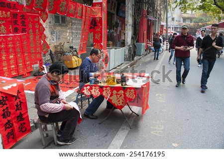 FOSHAN Feb 16:More than 30 calligraphers stall file write poetic couplet, attracted many people to buy, Chinese Spring Festival to paste the poetic couplet on the door Feb 16, 2015 in Foshan, China - stock photo