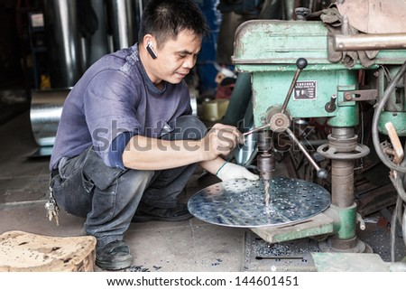 FOSHAN, GUANGDONG/CHINA - MARCH 16: Unidentified worker drills a metal plate in Shunde District of Foshan City, Guangdong Province, China on March 16th, 2013.  - stock photo