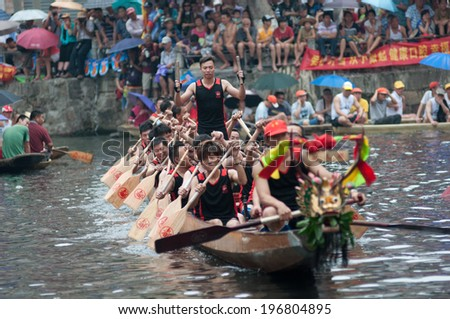 Foshan - Â?Â?June 3: The dragon boat competition held in Fenjiang River, 17 dragon boat to participate, attracting a large number of people to watch, Qingyun team won the first June 3, 2014 in Foshan, China - stock photo