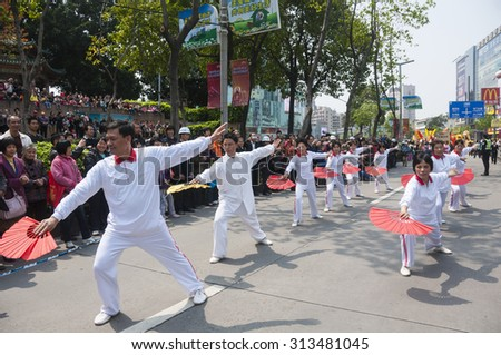FOSHAN, MARCH 23:In celebration of the temple of god birthday, Taoist believers parade held in traditional culture, kung fu fan performers took part in the parade  March 23, 2012 in Foshan, China - stock photo