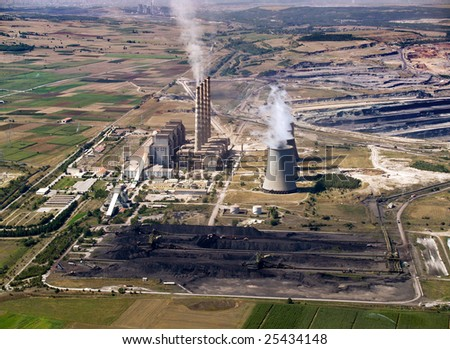 Fossil fuel power plant & coal piles, aerial view - stock photo