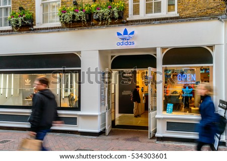 FOUBERT'S PLACE, LONDON - OCTOBER 26: The shop front of Adidas Originals store, people passing by. On Foubert's Place, off Carnaby Street, London, England on 26th October 2015.