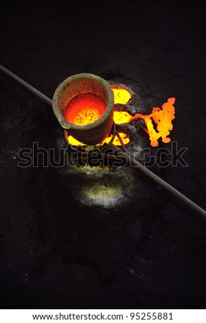 Foundry - molten metal in crucible standing on molds - leftover - stock photo