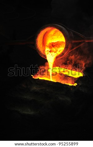 Foundry - molten metal poured from ladle into mold - emptying leftover - stock photo