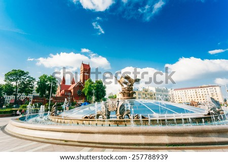 Fountain At Independence Square And Church Of Saints Simon And Helen (Red Church) In Minsk, Belarus - stock photo