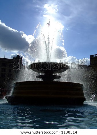 Fountain in a central London showered in sun - stock photo