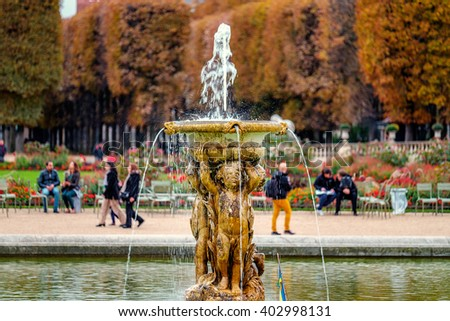 Fountain in Jardins du Luxembourg, Paris, France in autumn. Orange leafs and multicolored plants./Fountain in Jardins du Luxembourg, Paris, France - stock photo