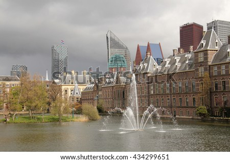 Fountain in the Hofvijver pond next to the Binnenhof governmet buildings and modern office buildings with the Dutch flag flying.