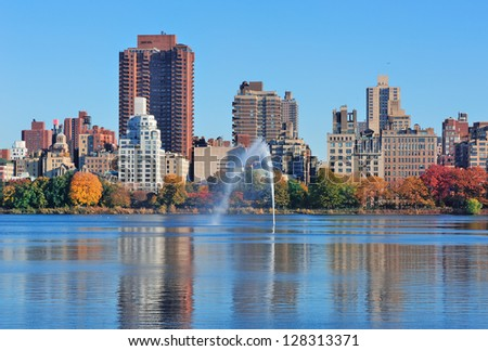 Fountain over lake in New York City Manhattan Central Park with skyscraper buildings and colorful Autumn foliage and clear blue sky.